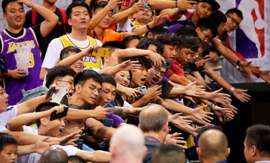 NBA洛杉磯湖人隊和布魯克林籃網隊2019年10月12日在中國深圳舉行的季前賽結束後,中國深圳球迷們紛紛伸出手等待與他們追捧的NBA球星握手。(STR/AFP via Getty Images)