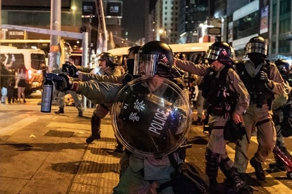 再有上萬名蒙面民眾上街抗議,港警大舉拘捕抗爭者及施放催淚彈,同時在多區真槍示警,直至午夜,衝突仍未平息。圖為港警向市民噴射胡椒水。(Anthony Kwan/Getty Images)