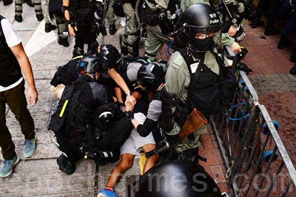 再有上萬名蒙面民眾上街抗議,港警大舉拘捕抗爭者及施放催淚彈,同時在多區真槍示警,直至午夜,衝突仍未平息,圖為一老人被摁倒在地。(宋碧龍/大紀元)
