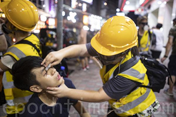 休班警被容許使用胡椒噴劑,抗爭市民更加處於不利境地。圖為9月8日有市民遭受催淚彈和胡椒噴劑,救護員為其清洗眼睛。(余鋼/大紀元)