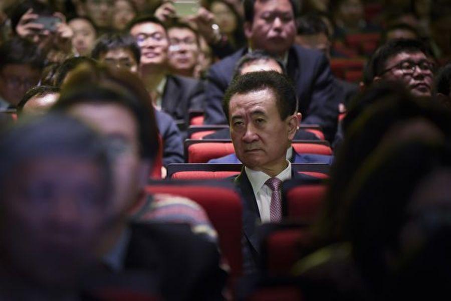 王健林旗下的萬達體育近來被美國多家律師事務所調查。圖為萬達集團董事長王健林(中)。(AFP)