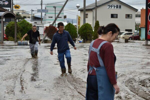 2019年10月14日,颱風過後,長野居民們在水災地區的泥濘道路上行走。(KAZUHIRO NOGI/AFP via Getty Images)