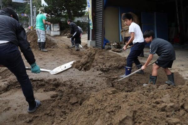 受到颱風侵襲影響,不少河川潰堤,河水消退後,居民開始清理家園。(JIJI PRESS/JIJI PRESS/AFP via Getty Images)