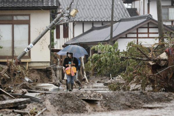 2019年10月14日,一名居民走過長野縣千曲河岸附近的颱風災區。( JIJI PRESS/JIJI PRESS/AFP via Getty Images)