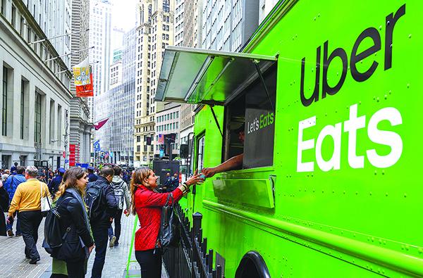 5月10日Uber上市首日,民眾從該公司停在紐約證交所外的餐車購買食物。(Getty Images)