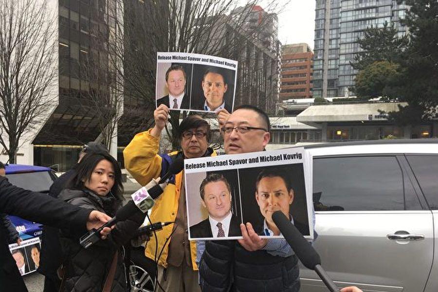 2019年3月6日,在卑詩高等法院進行華為財務總監孟晚舟引渡程序聽證時,人們手持被中共關押的兩名加拿大人康明凱( Michael Kovrig )和斯派沃(Michael Spavor )的照片,要求北京當局釋放他們。(余天白/大紀元)