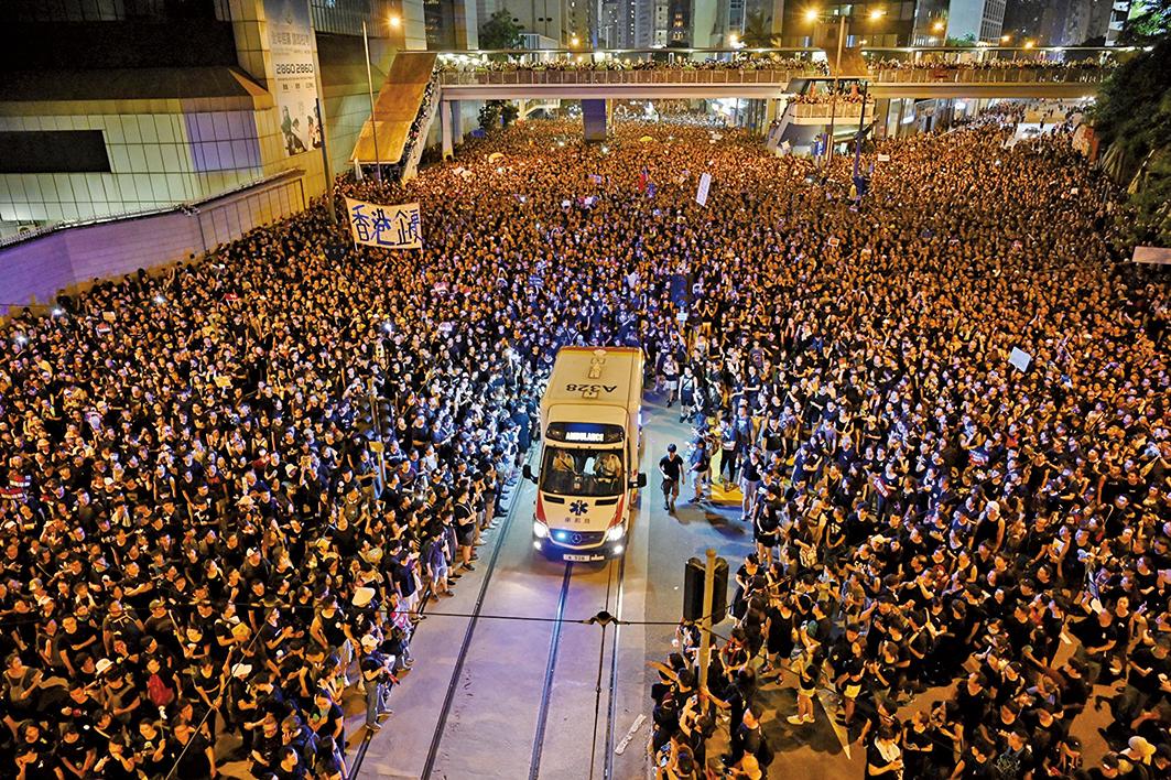 2019年6月16日,200萬港人遊行反送中。期間有救護車經過,民眾自動分開,之後人群又合上。這一幕被稱為港版「摩西分紅海」港人的和平、理性、高質素讓世人驚歎。(AFP)