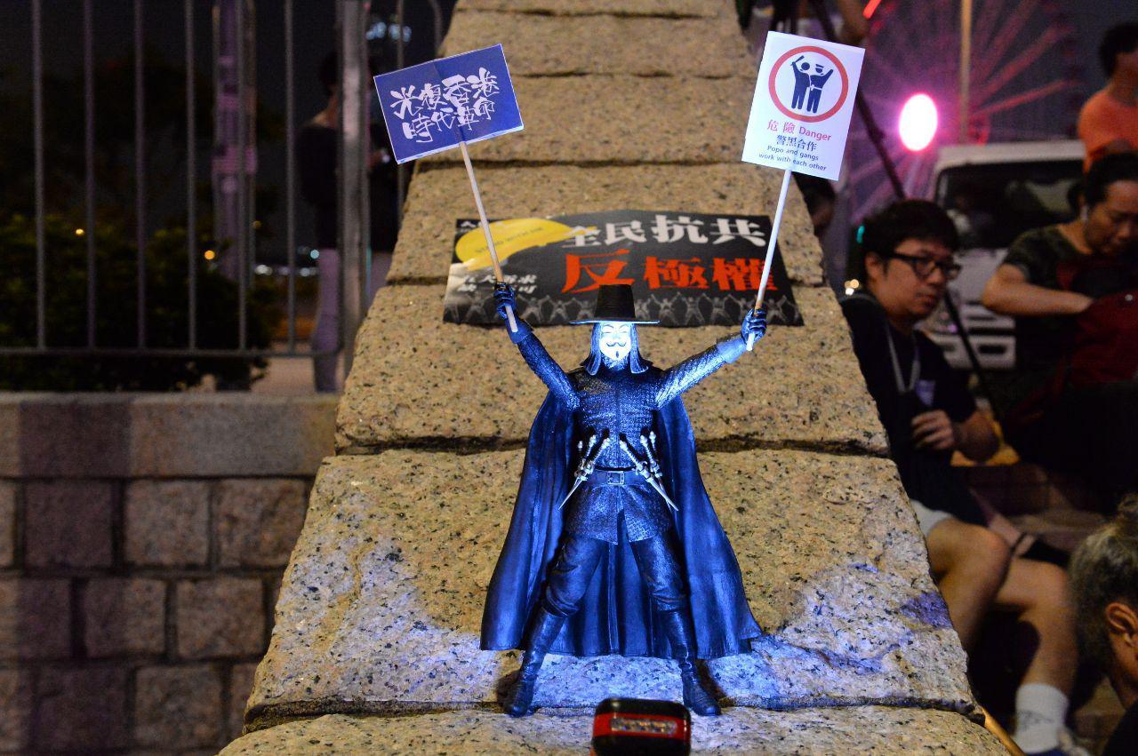 現場出現V剎公仔,兩手分別拿著「光復香港 時代革命」、「危險 Danger 、警黑合作」的牌(宋碧龍/大紀元)