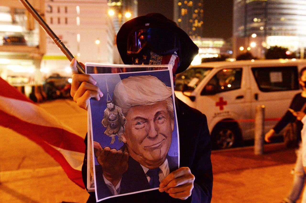 抗爭人士拿著印有特朗普像的單張(宋碧龍/大紀元)