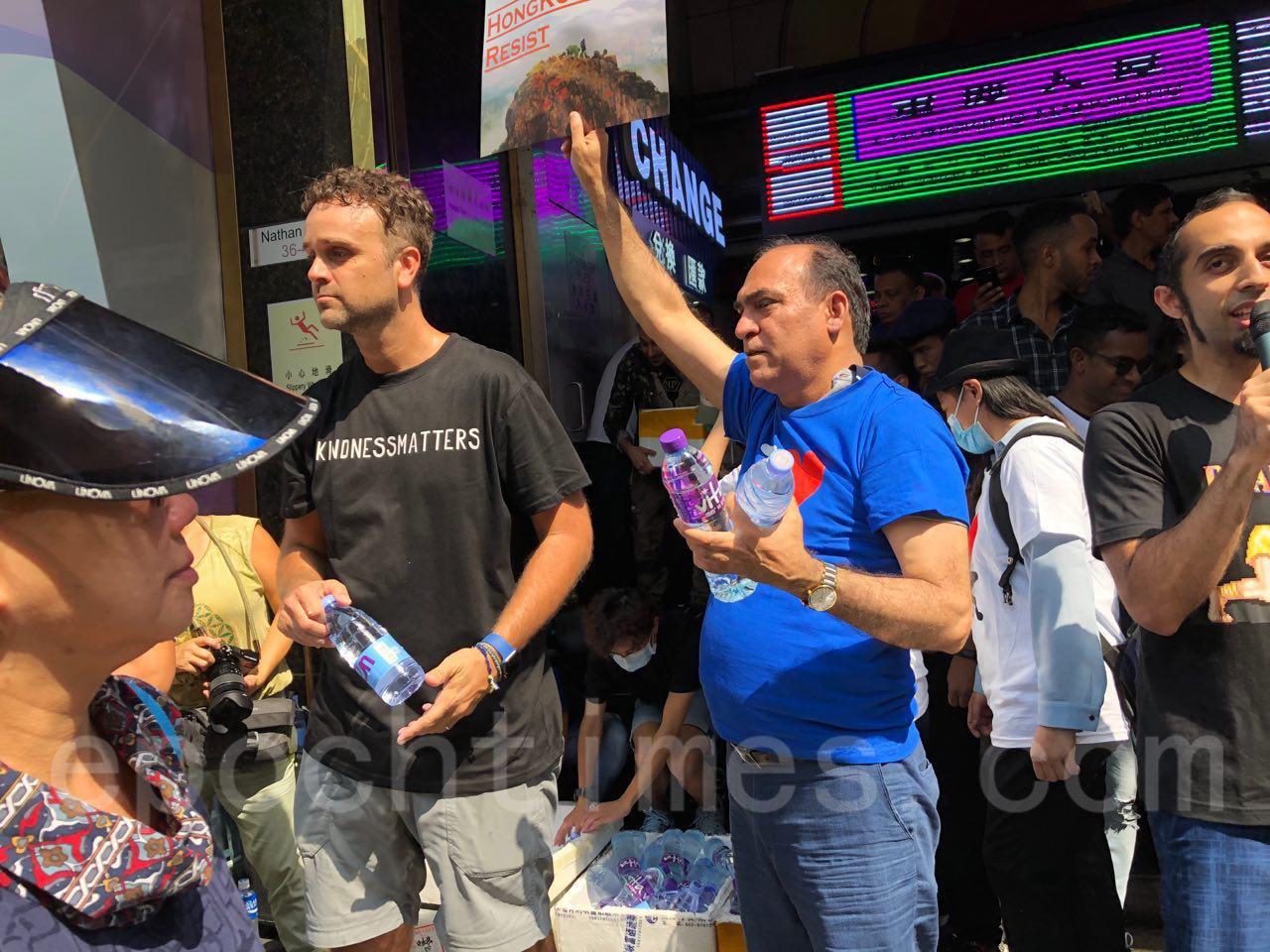 20日民陣發起的1020九龍大遊行在1時半左右出發。在南亞人聚集的重慶大廈附近,南亞人為遊行隊伍飲料水。(余天佑/大紀元)