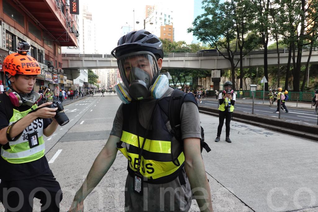 20日下午4時左右,在彌敦道與佐敦道交界附近水砲車向人群噴射藍色水。 多名市民和媒體記者被藍色水射中。突圍日媒記者被噴藍色水。(余鋼/大紀元)