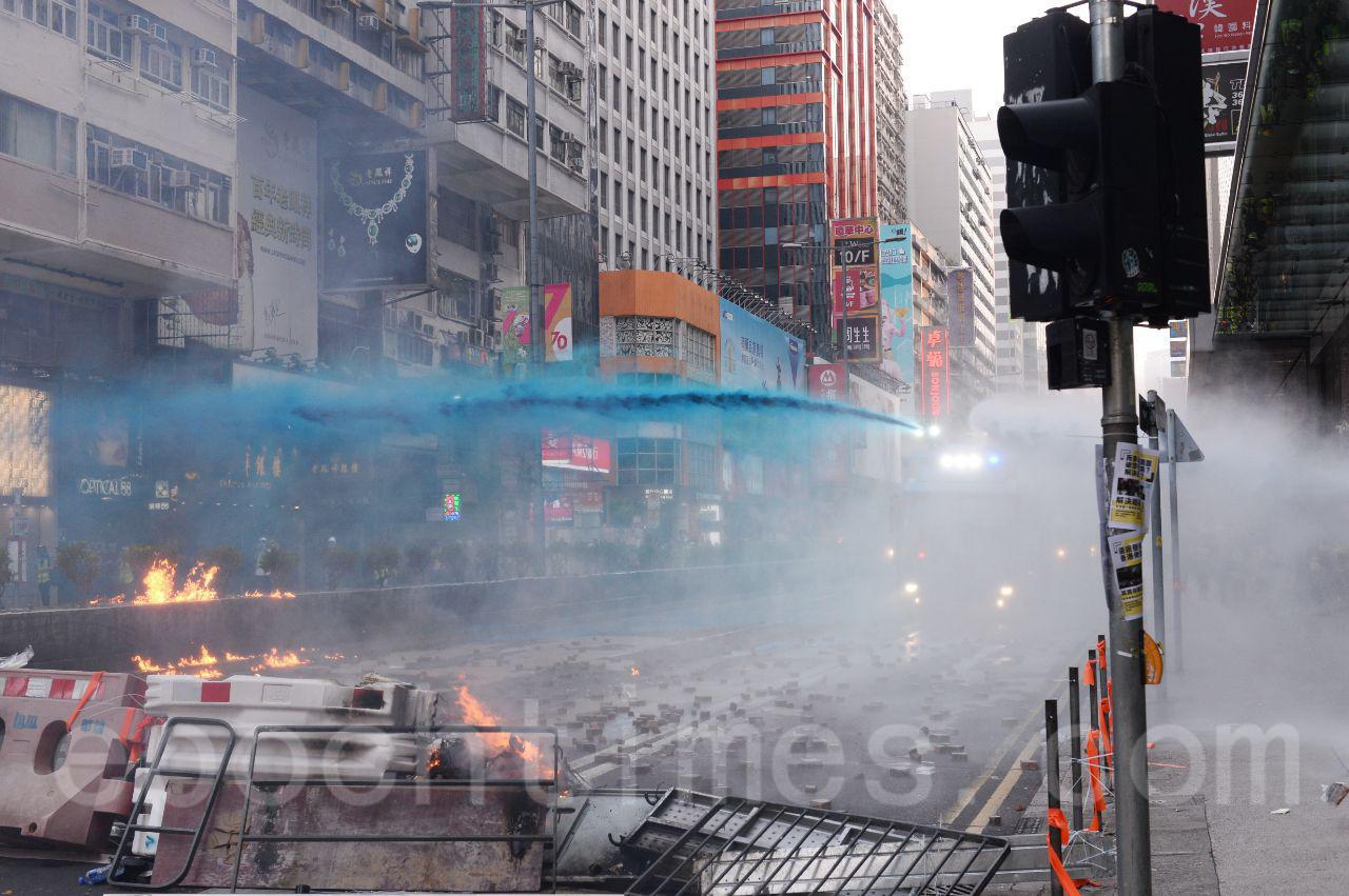 20日下午4時左右,在彌敦道與佐敦道交界附近水砲車向人群噴射藍色水。 多名市民和媒體記者被藍色水射中。突圍日媒記者被噴藍色水。(宋碧龍/大紀元)
