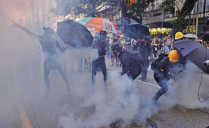 抗爭者將由尖沙咀警署發射到彌敦道上的催淚彈扔回警署。(宋碧龍/大紀元)