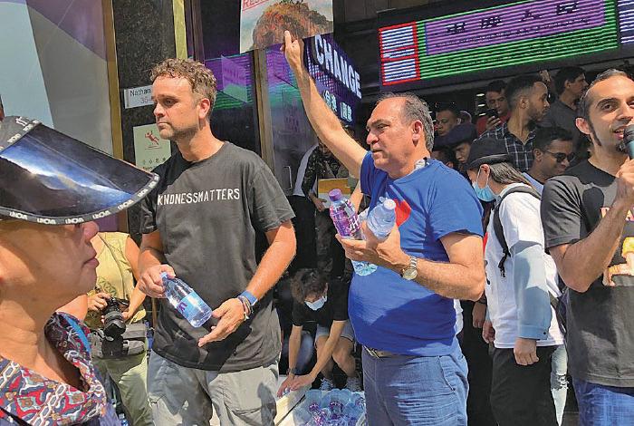 多名身穿「IHK」T恤的少數族裔人士在重慶大廈外派水,有人以流利廣東話高唱《海闊天空》等歌曲,又高呼「我哋都係香港人」。(余鋼/大紀元)