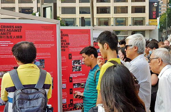 有市民上周六在尖沙咀文化中心外的公共地方,舉行「警方濫用暴力和侵犯人權展」,吸引很多市民和遊客駐足觀看。(駱亞/ 大紀元)