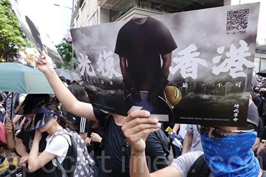2019年10月20日,香港九龍大遊行,市民步行到尖沙咀參加遊行。圖為民眾拿著「光復香港」標語。(駱亞/大紀元)