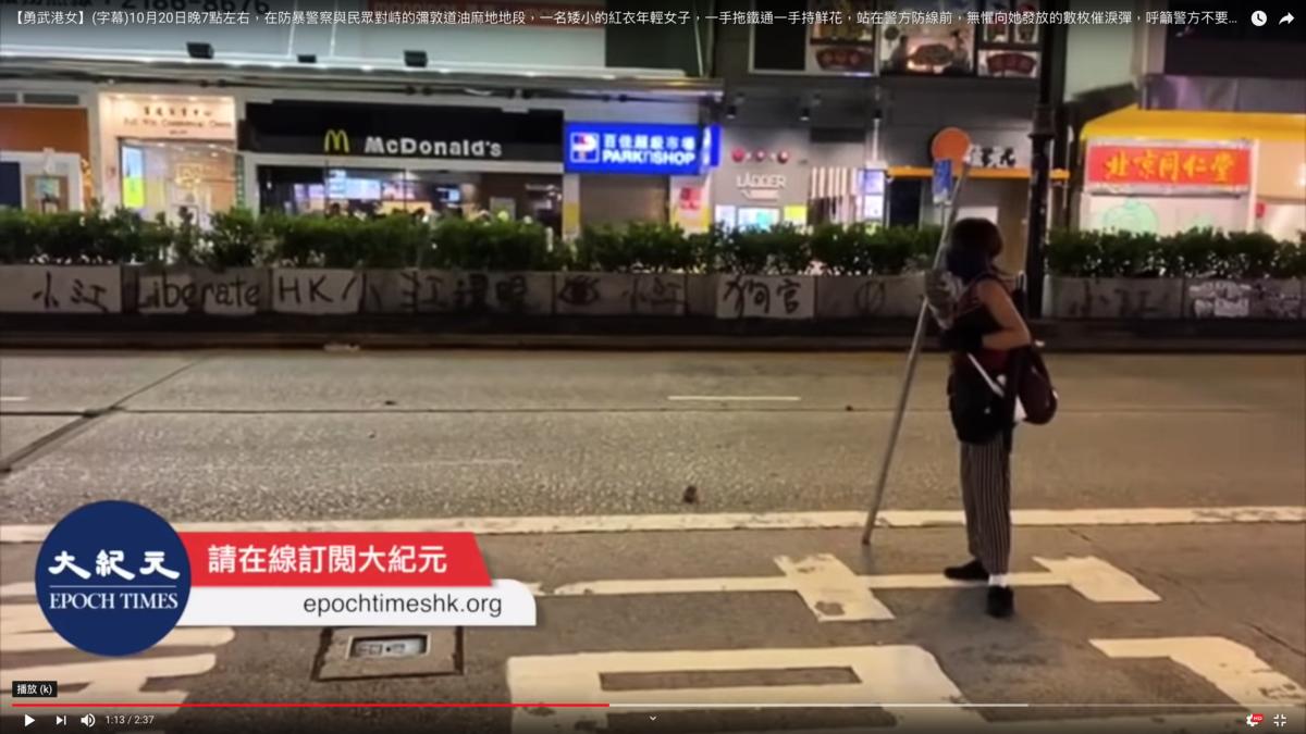 一名手持鮮花,拖著鐵通的平凡女子,面對警察的催淚彈高喊「你們不要再衝擊香港市民了!」(影片截圖)