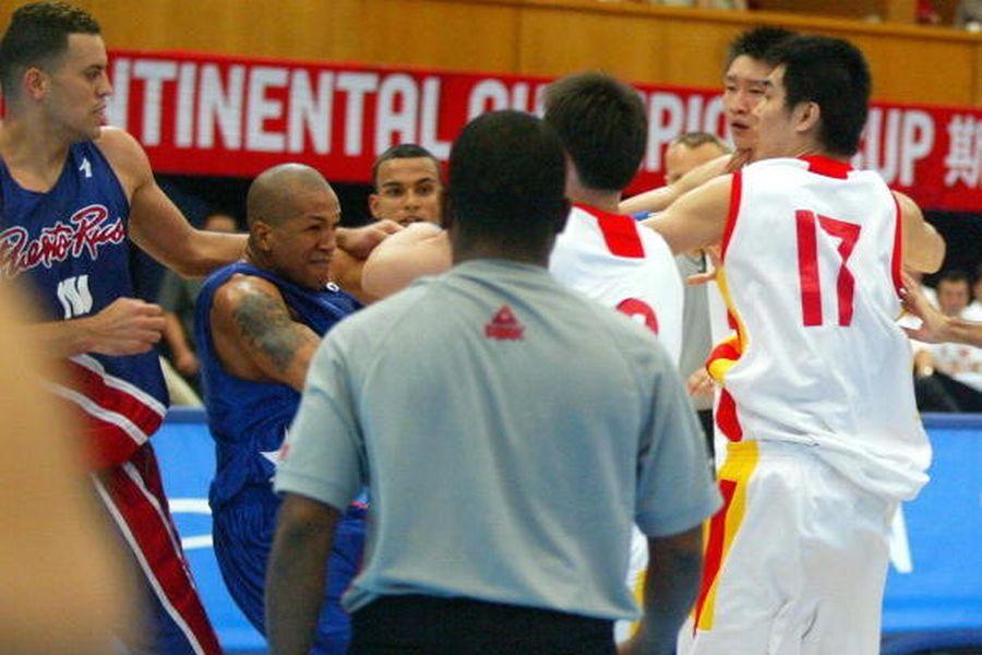 圖為2005年7月29日晚間在北京舉行的斯坦科維奇籃球洲際冠軍賽上,中國男籃隊球員易建聯與波多黎各隊中鋒爭搶籃板時,對方防守動作過激,臉上挨了一掌的易建聯衝動之下揚手反擊,最終演變為包括兩隊後備隊員在內的群毆。(AFP/Getty Images)