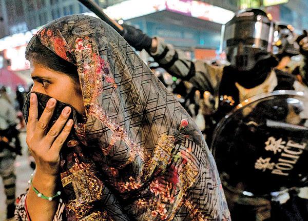 10月20日九龍大遊行,警方在油尖旺彌敦道沿途狂射催淚彈及藍色水劑。圖為一名少數族裔女子用圍巾掩鼻避催淚煙,後面的防暴警呼喝驅趕她。(Anthony Kwan/Getty Images)