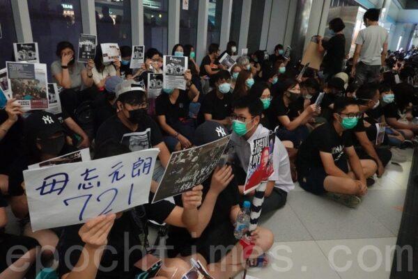 香港民眾在元朗西鐵站靜坐抗議,向乘客展示寫有「毋忘元朗721」等標語提醒市民毋忘元朗恐襲事件。(余鋼/大紀元)