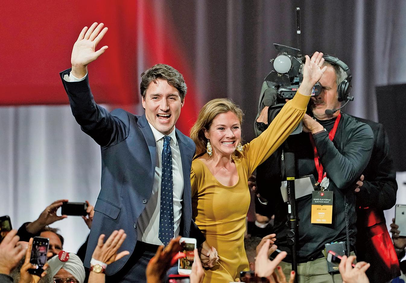 周二凌晨,自由黨領袖杜魯多和夫人索菲杜魯多在滿地可自由黨選舉總部,向支持者揮手致謝。(加通社)