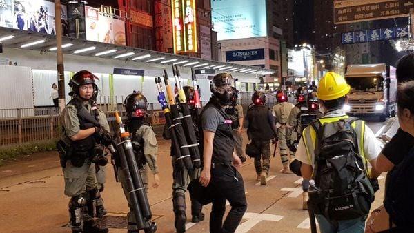 警方各個分隊行動時背旗的多了一個,除催淚彈警告外,還有背橙色開槍警告旗。(駱亞/大紀元)