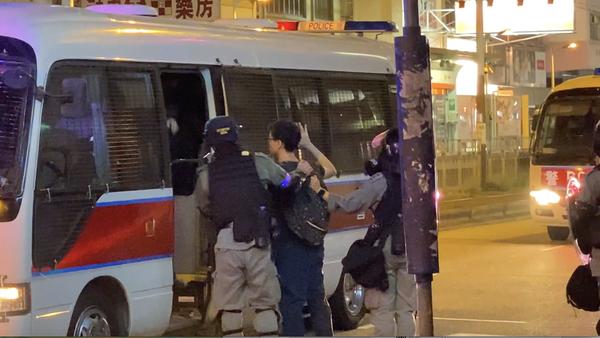 有一名學生模樣的戴眼鏡的男士被抓。(駱亞/大紀元)