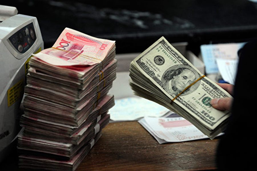 專家表示,即使美中兩國簽署第一階段貿易協議,人民幣兌美元匯率也將持續保持在7以上。圖為2010年3月9日,安徽省合肥市一家銀行的員工在點收人民幣和美元。(STR/AFP/Getty Images)