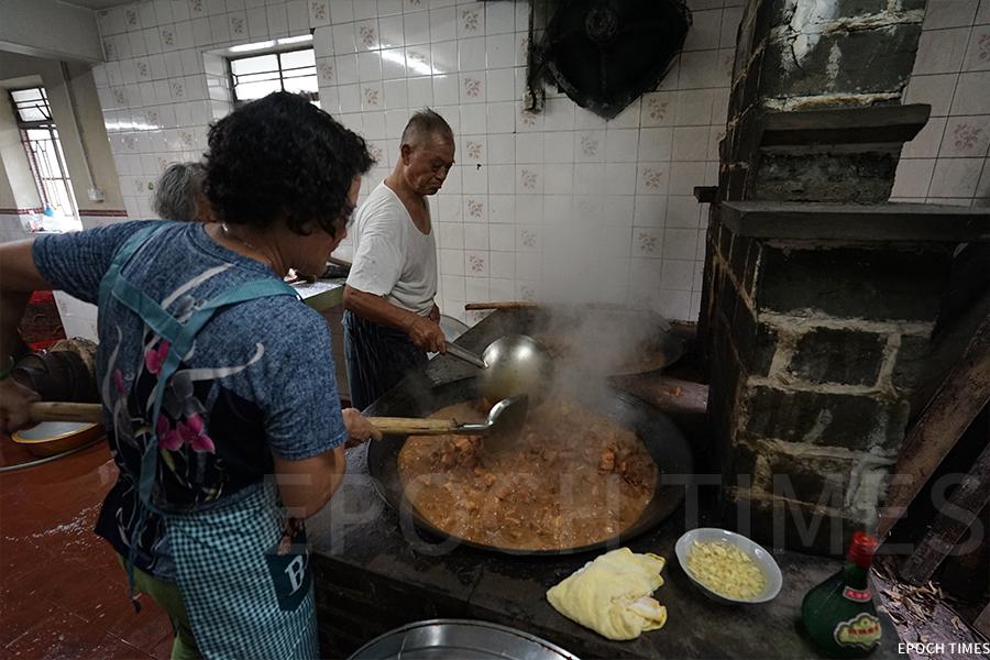 盆菜特色在於即場「打盆」,在宗祠內柴火烹飪。(曾蓮/大紀元)