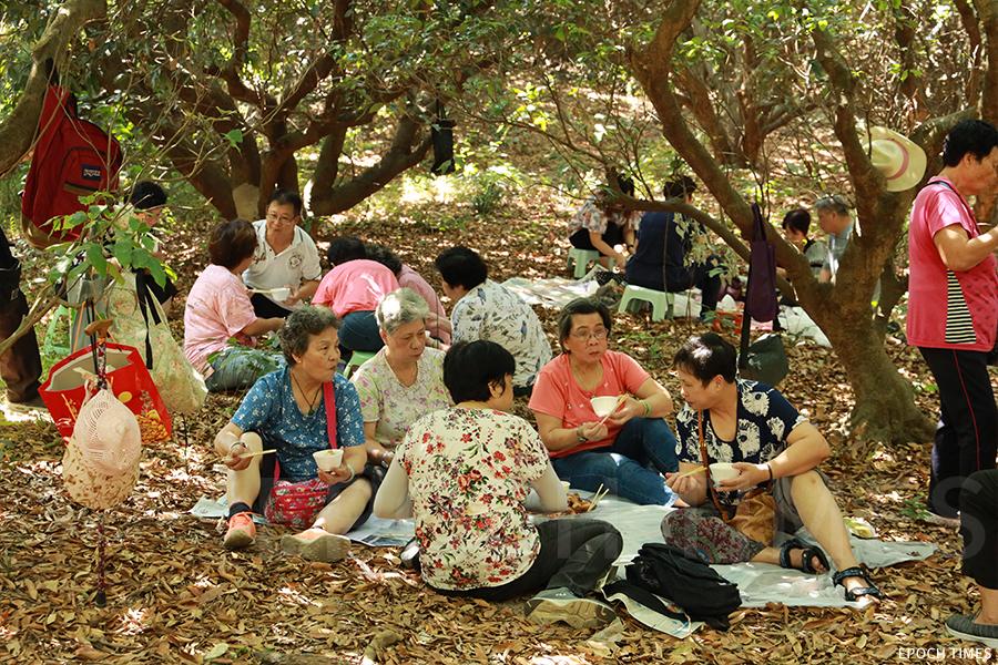 鄧氏族人席地而坐享用盆菜。(陳仲明/大紀元)