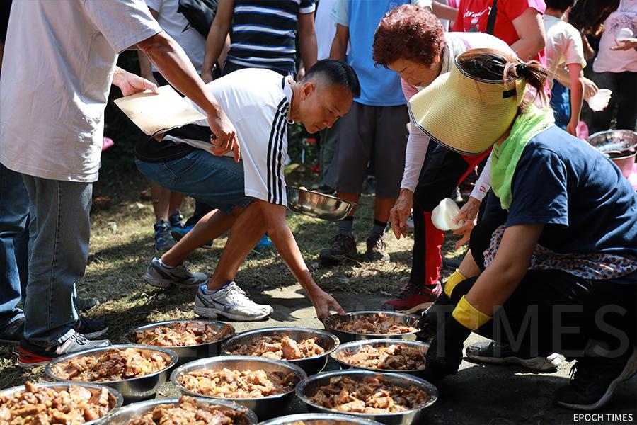 參加祭祀的族人憑票領取盆菜。(陳仲明/大紀元)