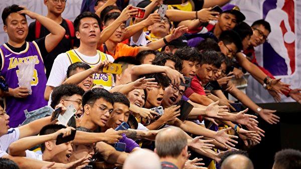 圖為10月12日,NBA深圳比賽爆滿,球迷熱情與球員互動。五毛試圖攪場沒人睬。(STR/AFP via Getty Images)