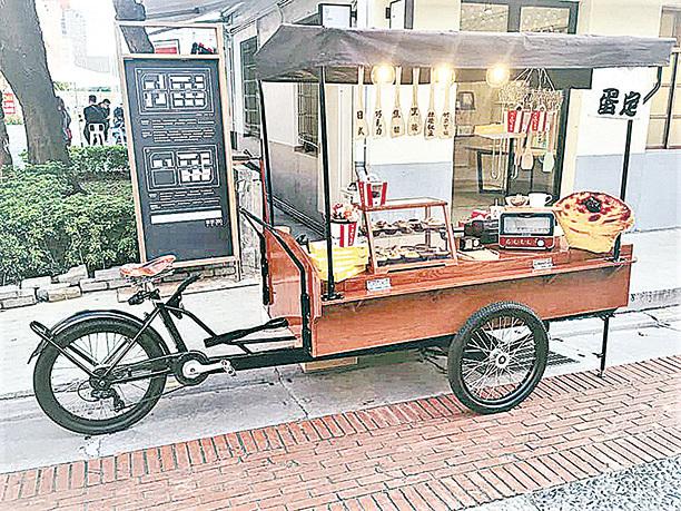 年輕老闆,推著一個木製的攤車在市集裏賣著蛋撻。