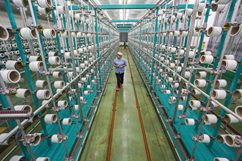 中國人民大學最新發佈報告表示,未來一段時間,中美貿易摩擦恐嚴重衝擊中國就業。圖為一名中國工人在江蘇省一家紡織廠內工作。(AFP/Getty Images)