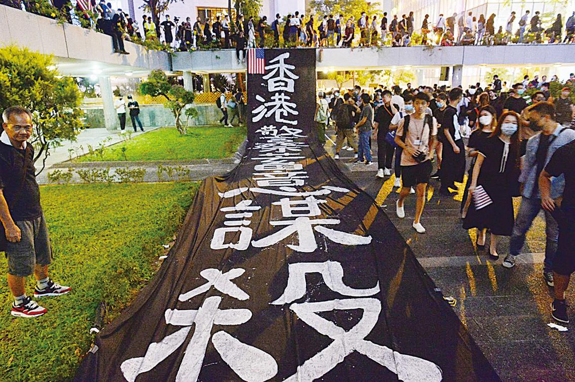 10月14日晚,在遮打花園的集會上,有市民鋪開大型橫幅:「香港警察 蓄意謀殺」,抗議警察過度使用武力。(宋碧龍/大紀元)