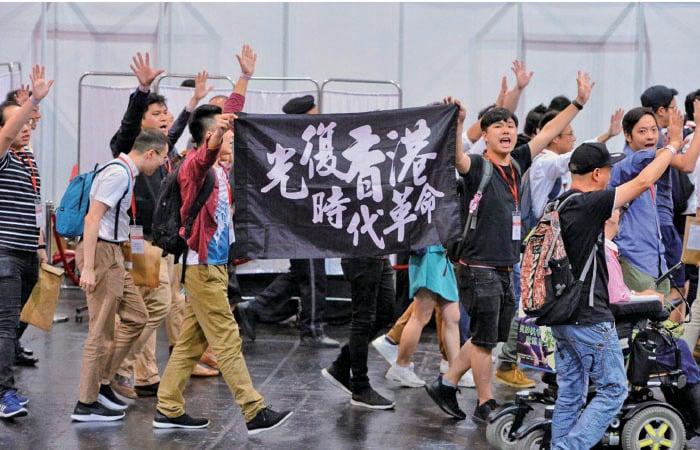 區議會選舉候選人簡介會腰斬後,民主派候選人手持「光復香港 時代革命」的標語和高叫口號,又舉起5隻手指,象徵「五大訴求,缺一不可」。(宋碧龍/大紀元)