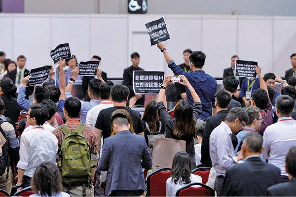黃之鋒晚上以選舉代理人身份,帶同標語進入候選人簡介會會場抗議。(宋碧龍/大紀元)