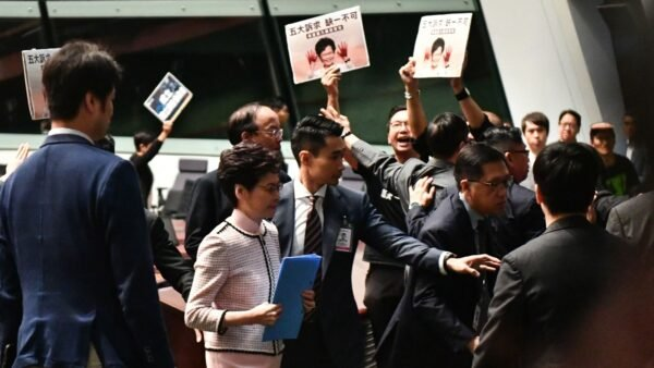 特首林鄭月娥16日到立法會宣讀《施政報告》,遭到民主派議員集體高喊口號抗議,有人更衝出座位抗議。(ANTHONY WALLACE/AFP via Getty Images)