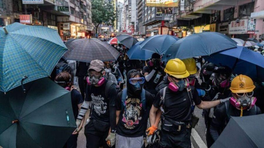 香港抗爭者於10月6日在金鐘區舉行了「反極權反緊急法大遊行」,面對前來進行鎮壓的警方,佩戴了防護面罩的抗爭者紛紛撐起雨傘準備抵禦警方發射的催淚彈。(Anthony Kwan/Getty Images)