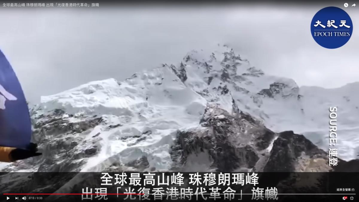 不久前,兩位不知名人士將寫有「光復香港,時代革命」的旗幟展現在了世界的最頂峰——珠穆朗瑪峰上。(影片截圖)