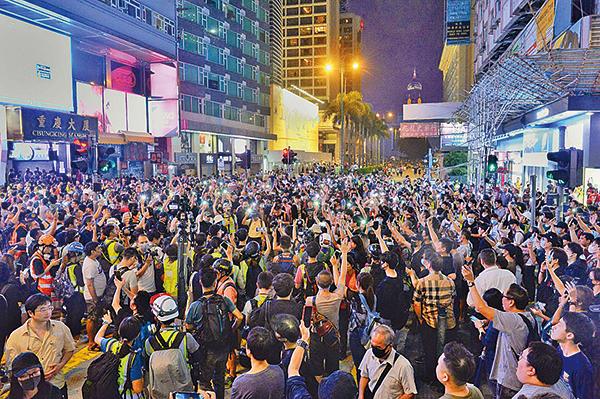 昨日入夜後被驅散的市民再聚集在重慶大廈前的彌敦道,並用手機燈海照亮黑夜,表達「五大訴求,缺一不可」。( 宋碧龍/大紀元)