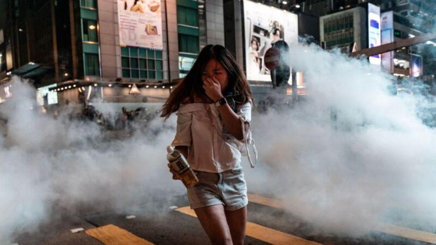 香港警方於2019年10月27日在香港旺角區發射催淚彈後,一名行人從催淚煙霧中摀住口鼻跑出。(Anthony Kwan/Getty Images)