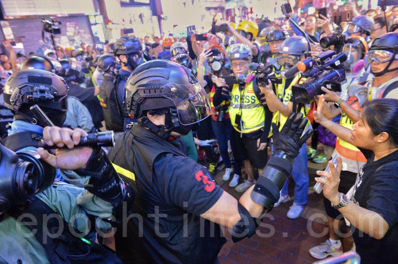 香港市民在4個多月抗暴政,爭自由的運動中,遭到港警不斷升級的暴力鎮壓,圖為27晚在旺角警方數度與記者、民眾衝突,遭民眾駡是「黑社會,走狗」。(宋碧龍/大紀元)