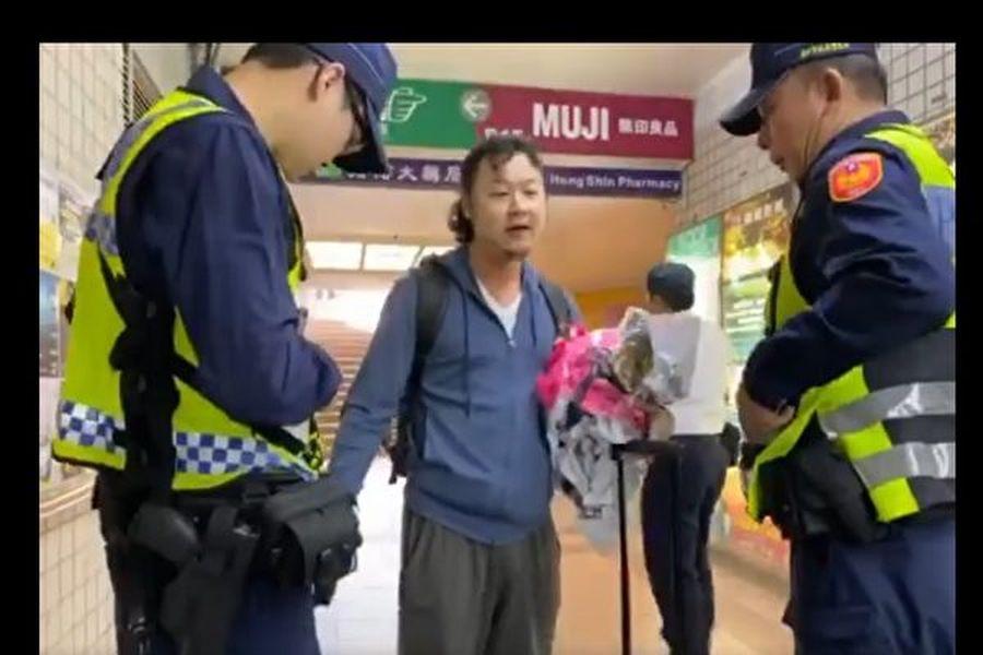 中國遊客因破壞台中市一處連儂牆,被台灣警方帶走。(影片截圖)