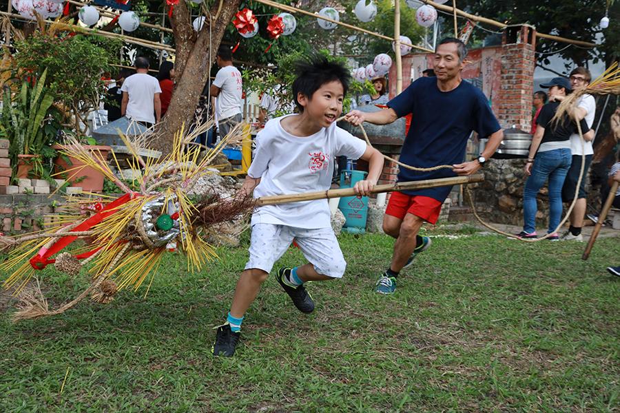 九歲的蕭震南(前)是蕭昆崙(後)的兒子,對舞龍充滿了熱忱。(陳仲明/大紀元)