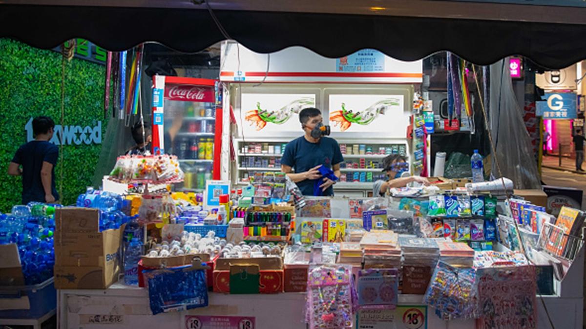 香港小商家店主戴著防毒面具在售貨。(Billy H.C. Kwok/Getty Images)