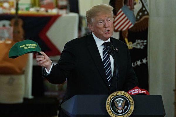 圖為特朗普2018年7月23日在白宮的「美國製造」商品展活動中,手持「讓我們的農民再次強大」的帽子。(Alex Wong/Getty Images)