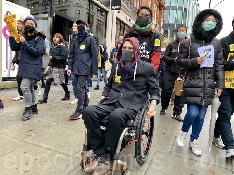 有行動不便的外籍人士坐著輪椅完成整個遊行。(唐詩韻/大紀元)