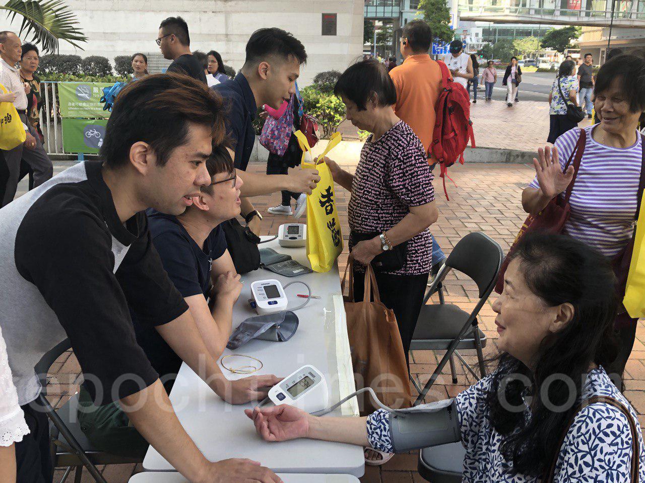 11月3日,在荃灣發起向關懷長者的活動。圖為為長者量血壓。(余天佑/大紀元)