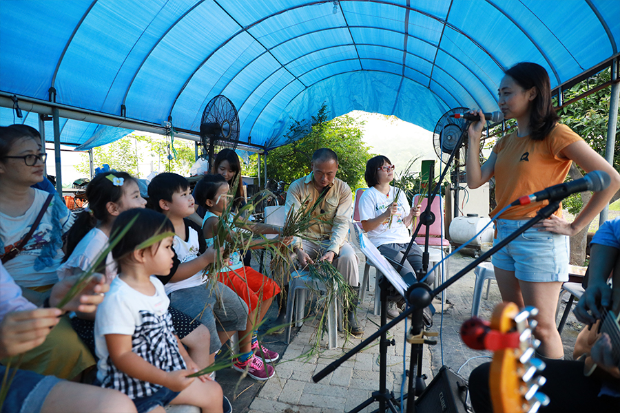 小朋友們伴隨著歌聲一起揮舞著手中的稻草。(陳仲明/大紀元)